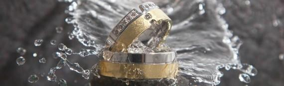 Trauringe aus Gelbgold mit Kante aus Weißgold, der Damenring mit mehreren Brillanten ausgestattet.